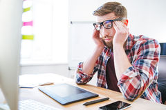 Uomo esaurito stanco che si siede sul posto di lavoro e sulle tempie commoventi Fotografia Stock Libera da Diritti