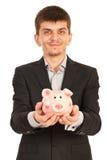 Uomo esecutivo felice con il porcellino salvadanaio Fotografia Stock