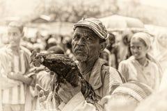 Uomo etiopico anziano che vende un gallo in un mercato Immagini Stock