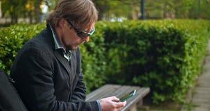 Uomo europeo facendo uso dello smartphone in parco archivi video
