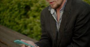 Uomo europeo facendo uso dello smartphone in parco video d archivio