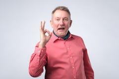 Uomo europeo senior nel segno GIUSTO di rappresentazione rossa della camicia immagini stock libere da diritti