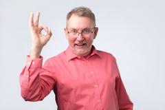 Uomo europeo senior nel segno GIUSTO di rappresentazione rossa della camicia fotografie stock
