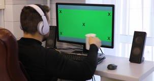Uomo facendo uso del computer del PC con la chiave verde di intensità dello schermo a casa video d archivio