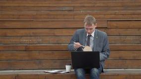 Uomo facendo uso del computer portatile all'aperto mentre pranzando stock footage
