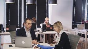 Uomo facendo uso del computer portatile e della discussione del progetto nuovo con la donna video d archivio