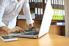 Uomo facendo uso del computer portatile e lavorare alla tavola in ufficio immagini stock libere da diritti