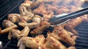 Uomo facendo uso dell'tenaglie a girare le ali di pollo piccanti deliziose sul barbecue della griglia archivi video