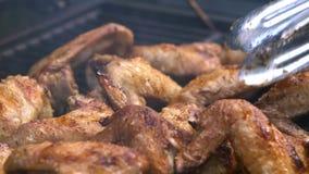 Uomo facendo uso dell'tenaglie a girare le ali di pollo piccanti deliziose sul barbecue della griglia stock footage
