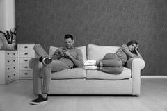 Uomo facendo uso dello smartphone e della trascuratezza della sua amica, effetto in bianco e nero Concetto di solitudine immagine stock libera da diritti
