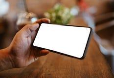 Uomo facendo uso di Smartphone alla caffetteria Telefono cellulare dello schermo in bianco per il montaggio del dispositivo grafi fotografie stock libere da diritti