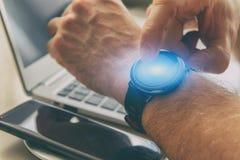 Uomo facendo uso di smartwatch in ufficio immagine stock libera da diritti