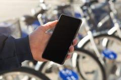 Uomo facendo uso di un telefono cellulare davanti alla stazione della bicicletta fotografia stock