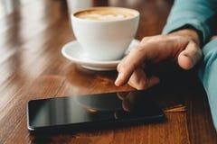Uomo facendo uso di uno smartphone e bere il fondo del caffè immagini stock libere da diritti