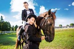 Uomo facente una pausa della donna premurosa che si siede sul cavallo al campo Immagini Stock