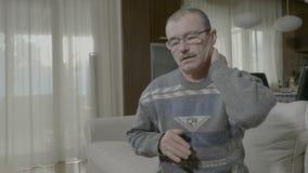 Uomo fatto soffrire pensionato che massaggia il suo indietro del collo a guarire il dolore a casa che soffre dallo sforzo del mus video d archivio
