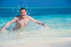 Uomo felice in acqua con la spruzzata dell'acqua Fotografia Stock