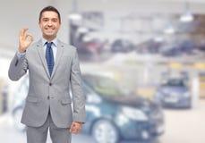 Uomo felice al salone dell'automobile o dell'esposizione automatica Fotografia Stock Libera da Diritti