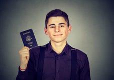 Uomo felice bello del ritratto giovane con il passaporto di U.S.A. Immagini Stock Libere da Diritti