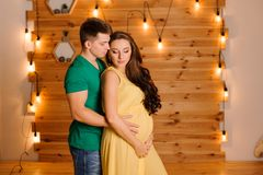 Uomo felice che abbraccia la sua bella moglie incinta sui precedenti della ghirlanda immagini stock