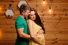 Uomo felice che abbraccia la sua bella moglie incinta sui precedenti della ghirlanda fotografia stock libera da diritti
