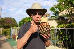Uomo felice che beve dall'ananas Fotografia Stock