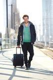 Uomo felice che cammina sul binario della stazione ferroviaria con la borsa Fotografie Stock