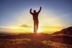 Uomo felice che celebra successo di conquista contro il tramonto immagini stock libere da diritti