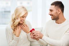 Uomo felice che dà anello di fidanzamento alla donna a casa fotografie stock