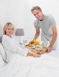 Uomo felice che dà prima colazione a letto al suo partner Fotografia Stock