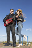 Uomo felice che gioca chitarra acustica con la donna che tiene il suo cappello fotografia stock libera da diritti