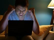 Uomo felice che guarda qualcosa su un computer portatile vincita immagini stock libere da diritti