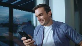 Uomo felice che guarda telefono cellulare Uomo bello che guarda foto sul cellulare stock footage
