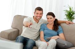 Uomo felice che guarda TV con la sua seduta dell'amica Fotografie Stock Libere da Diritti