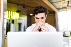 Uomo felice che lavora al computer portatile ed allo sguardo di pensiero allo schermo Immagini Stock