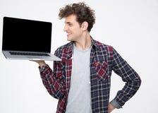 Uomo felice che mostra lo schermo in bianco del computer portatile Immagine Stock Libera da Diritti