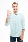 Uomo felice che mostra segno giusto con le dita sopra fondo bianco Fotografia Stock