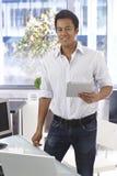 Uomo felice che per mezzo del computer della compressa Fotografia Stock Libera da Diritti