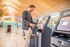 Uomo felice che per mezzo della macchina di registrazione all'aeroporto che ottiene immagini stock
