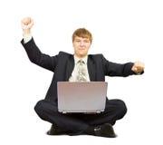 Uomo felice che per mezzo di un computer portatile Immagine Stock Libera da Diritti