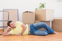 Uomo felice che posa con le scatole commoventi a casa Fotografia Stock