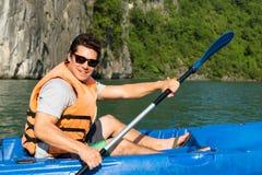Uomo felice che rema un kajak sull'oceano immagini stock