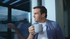 Uomo felice che resta vicino alla finestra dopo il giorno lavorativo Uomo rilassato che ha resto archivi video