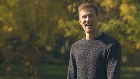 Uomo felice che ride e che mostra i pollici sull'aria aperta, occupazione, sicurezza sociale video d archivio