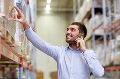 Uomo felice che rivolge allo smartphone al magazzino Fotografie Stock