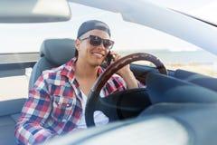 Uomo felice che rivolge allo smartphone in automobile convertibile Immagini Stock