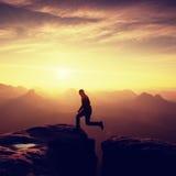 Uomo felice che salta fra le rocce, montagne nebbiose Fotografia Stock