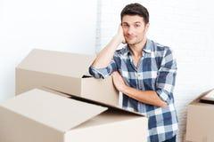 Uomo felice che si muovono dentro e contenitori di trasporto di cartone fotografia stock libera da diritti