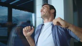 Uomo felice che si rilassa dopo il giorno lavorativo Uomo sorridente che prova ad allungare video d archivio