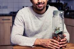 Uomo felice che si siede nella cucina con il porcellino salvadanaio Fotografie Stock Libere da Diritti